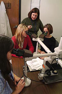 students and professor looking through microscopes